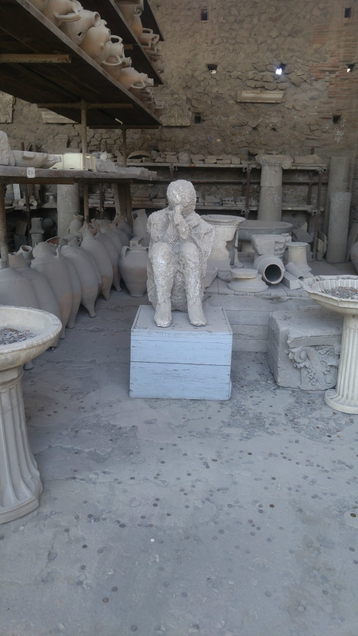 Plaster cast of man covering his face in Pompeii